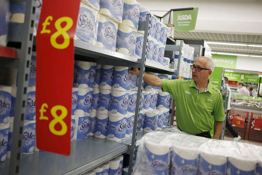 An employee stocks toilet paper along an aisle of an Asda store in Kendal, northwest England, Britain on Aug 30, 2015.