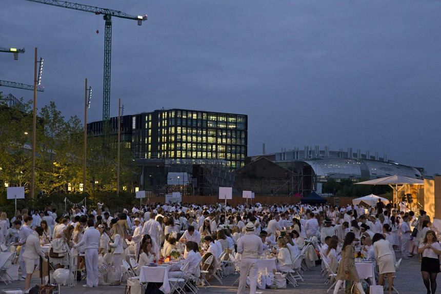 """Participants dressed all in white attend a """"Diner en Blanc"""" or """"Diner in White"""" in the King's Cross area of London on Sept 3, 2015."""