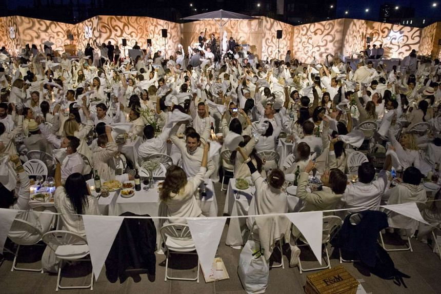"""Participants dressed all in white wave their napkins to signal the beginning of the meal as they attend a """"Diner en Blanc,"""" or """"Diner in White,"""" in the King's Cross area of London on Sept 3, 2015."""