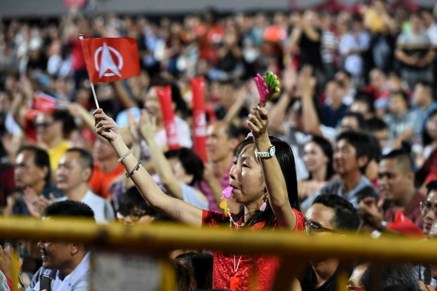 A Singapore Democratic Party (SDP) supporter waving the party flag as SDP secretary-general Chee Soon Juan (not in picture) speaks at the Chua Chu Kang stadium during a rally on Sept 3.