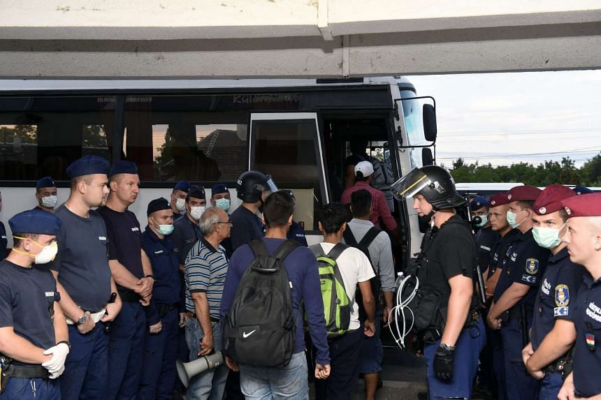 Migrants being escorted from a train to a bus by police at the railway station in Bicske, Hungary, on Sept 4, 2015.
