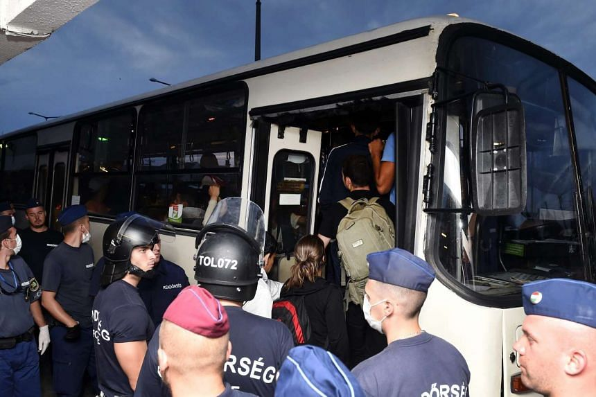 Migrants are escorted from the train to a bus by police at the Railway Station in Bicske, Hungary on Sept 4, 2015