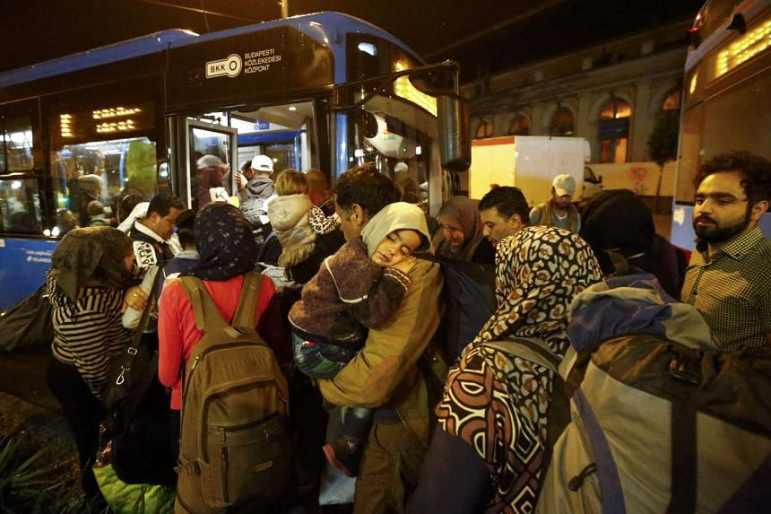 Migrants entering a bus, which is supposed to leave for Austria and Germany, at the Keleti train station in Budapest, Hungary, on Sept 4, 2015.