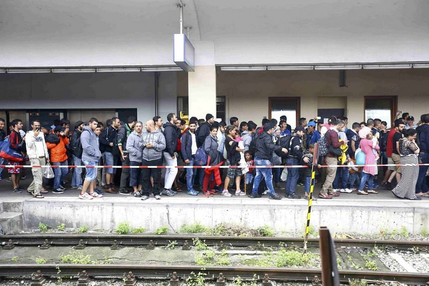 Migrants walking along a platform after disembarking from a train in Vienna, Austria, on Sept 5, 2015.