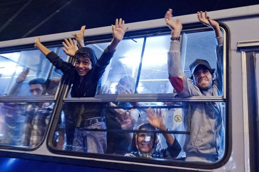Migrants waving from a bus as they wake up to a new dawn in East Railway Station in Budapest, Hungary, on Sept 5, 2015.