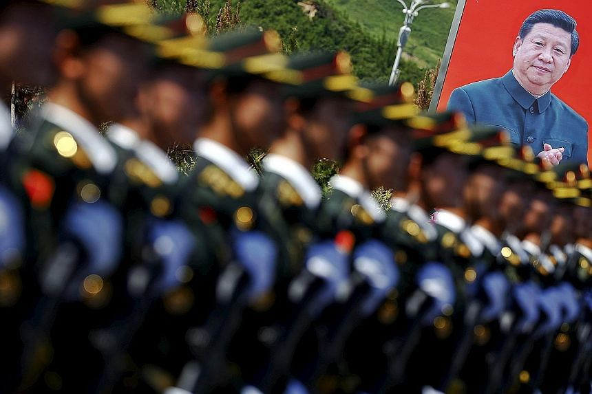 Soldiers of the People's Liberation Army marching in front of a poster of Chinese President Xi Jinping during a training session in August. Mr Xi on Thursday announced the unexpected reduction of 300,000 troops, which is said to be part of broader re