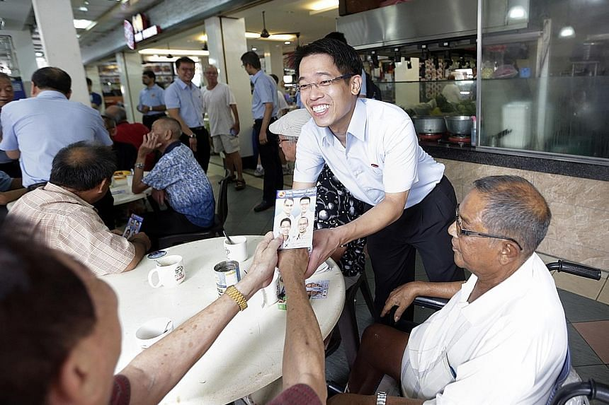 WP's candidate for East Coast GRC, Mr Gerald Giam, distributing fliers at the New Upper Changi Road Market and Food Centre yesterday while on a walkabout with his team.