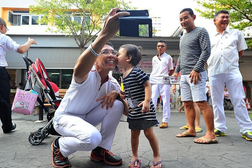 PAP's Dr Mohamad Maliki Osman getting a kiss on the cheek from two-year-old Ng Kai Xuan during the PAP East Coast GRC team's walkabout in New Upper Changi Road yesterday.