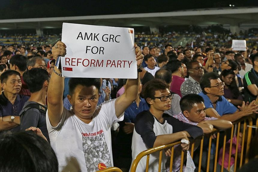 A Reform Party supporter holding up a card during the party's rally at Yio Chu Kang Stadium yesterday.