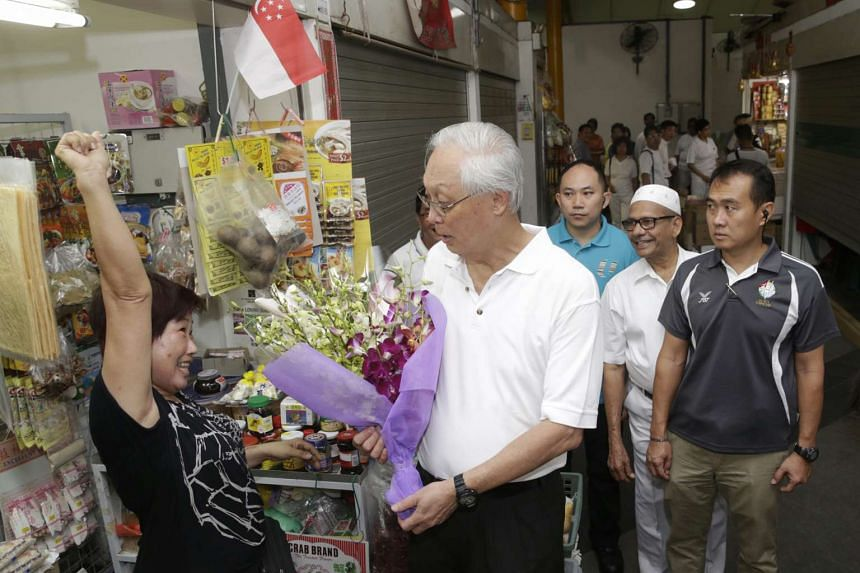 """Madam Lim Eng Lye, 60, who sells vegetarian foodstuff, says, """"I hope you get elected!"""", after presenting PAP Marine Parade GRC candidate Emeritus Senior Minister Goh Chok Tong a bouquet of flowers at Eunos Crescent Market and Food Centre on Sept 5, 2"""