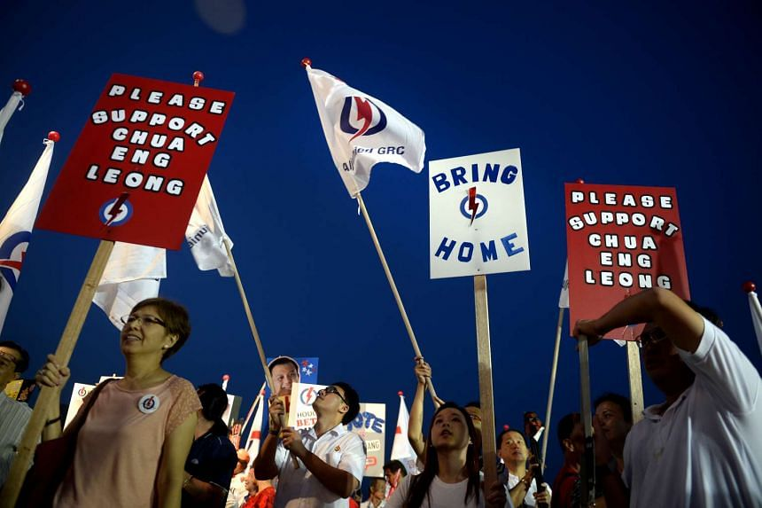 Supporters at last night's PAP rally in Aljunied GRC (above), held on a field in Defu. Among the crowd were eight-month-old Emma Ingkiriwang, with her father Ryan and mother Fiona, both 31, donning homemade outfits with the PAP logo.