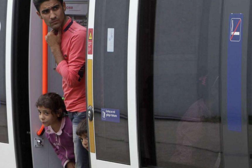 Migrants look out from a train at the railway station in Nickelsdorf, Austria, on Sept 5, 2015. Austria and Germany threw open their borders to thousands of exhausted migrants on Saturday,
