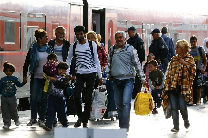Migrants walk along a train after arriving to the main railway station in Munich, Germany, on Sept 5, 2015.