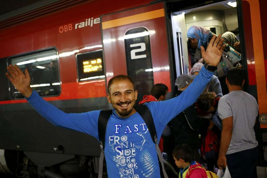 A migrant arriving from Hegyeshalom, Hungary, gestures as he leaves the train at the railway station in Vienna, Austria, on Sept 5, 2015.