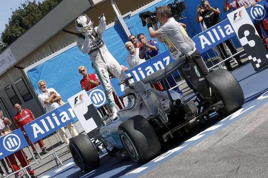 British Formula One driver Lewis Hamilton of Mercedes AMG GP celebrates after winning the 2015 Formula One Grand Prix of Italy at the Formula One circuit in Monza, Italy, on Sept 6, 2015.