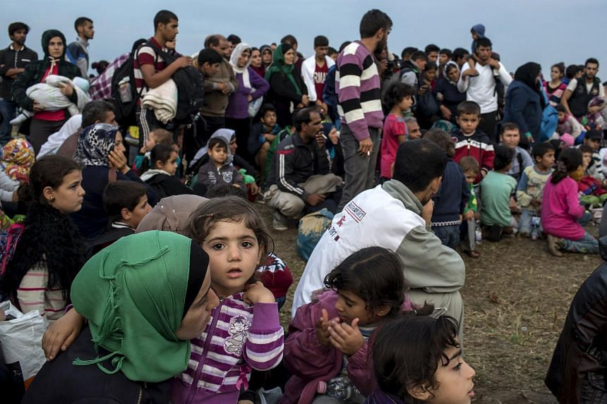 Migrants from Syria wait for a bus after crossing into Hungary from the border with Serbia on a field near the village of Roszke, on Sept 5, 2015.