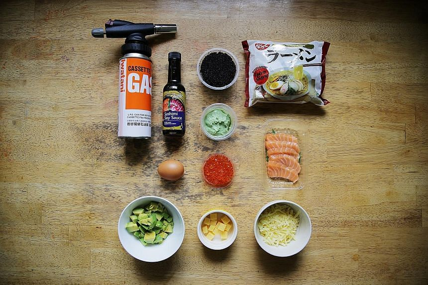 From top row: blow-torch, sashimi soya sauce, lumpfish caviar, instant ramen, wasabi, egg, salmon roe, salmon sashimi, avocado, tamago and grated cheese. Mr Jonathan Loong plans to make a chicken rice version of the ramen pizza as a tribute to his Ha
