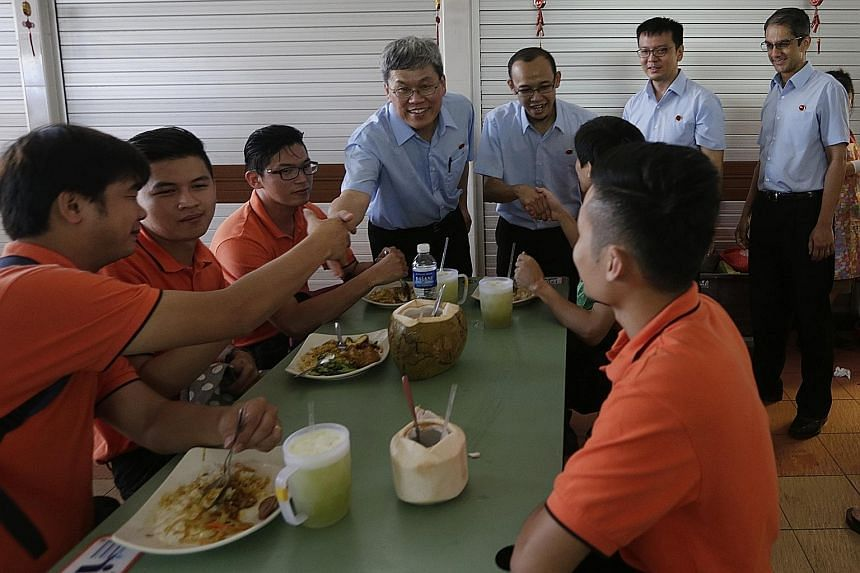 Mr Png Eng Huat (centre) with Workers' Party candidates for East Coast GRC (from left) Fairoz Shariff, Daniel Goh and Leon Perera at their walkabout in Changi Village yesterday.