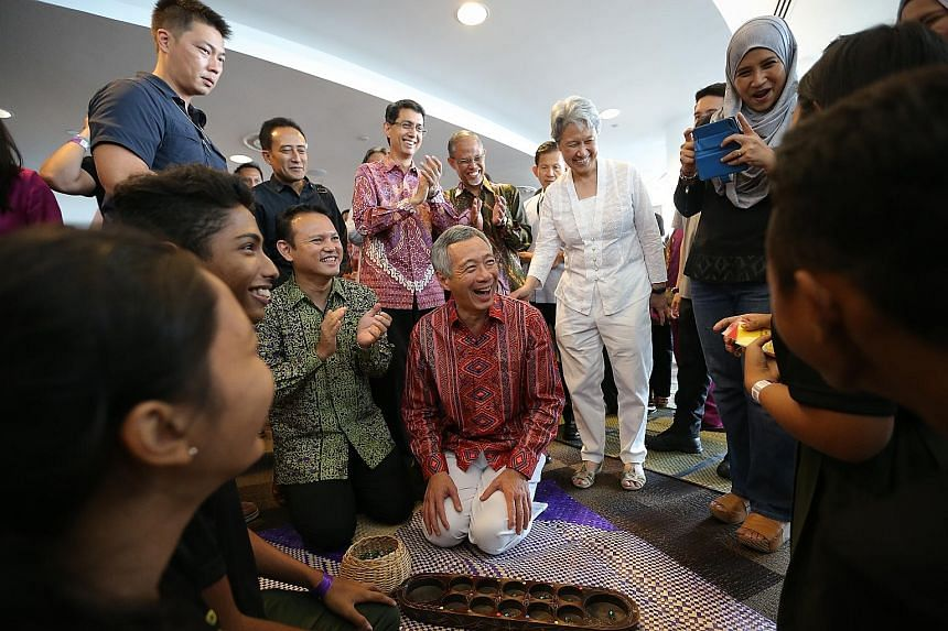 PM Lee Hsien Loong playing an improvised game of congkak integrated with language and culture with students from Orchid Park Secondary School, while his wife Ho Ching and Mr Zaqy Mohamad (next to him) look on. Mr Lee was attending the launch of Malay
