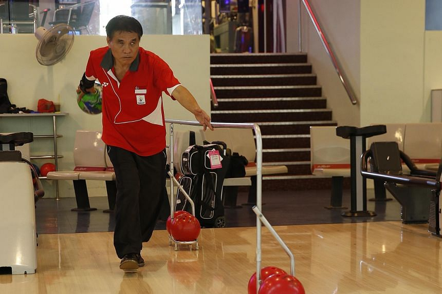 Thomas Yong, who is blind, bowls with the help of a guide rail.