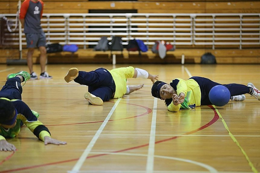 Despite being visually impaired, goalball athletes such as Kelvin Tan (right) are able to hear the bell inside the ball and block their opponent's goal attempts.