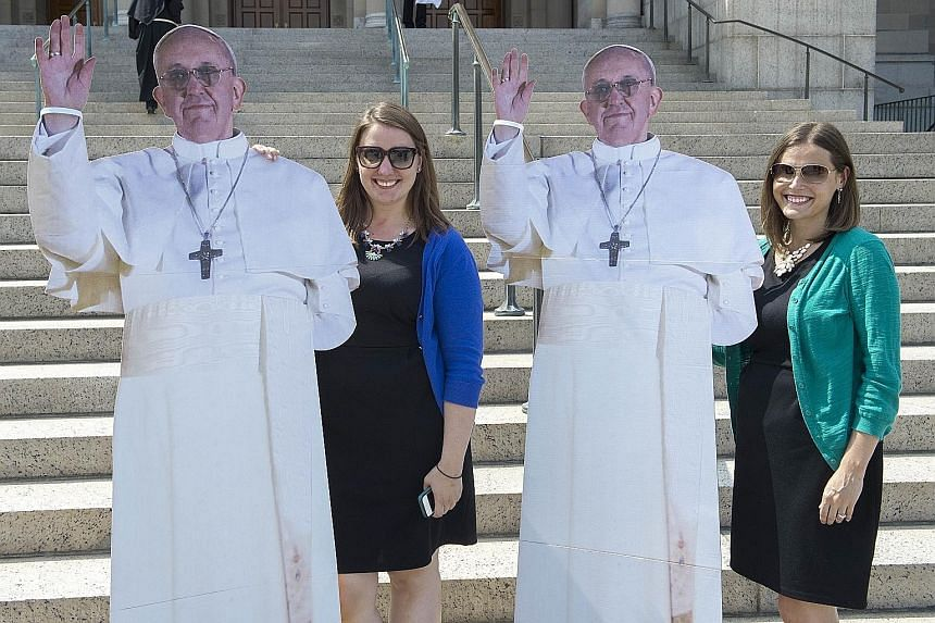 Left: A bicycle-cab bearing a welcome message for Pope Francis in Havana, Cuba. Above: Visitors at the Basilica of the National Shrine of the Immaculate Conception posing with life-sized images of the Pope in Washington, DC.
