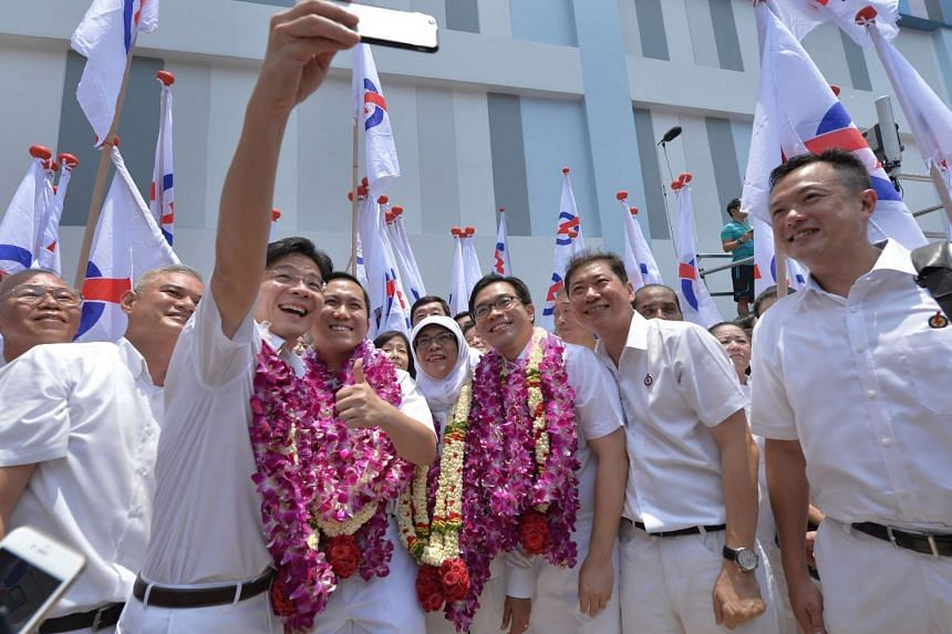 PAP candidates, including Mr Lawrence Wong (left wearing garland) for Marsiling-Yew Tee GRC take a selfie at the nomination centre on Sept 1, 2015.