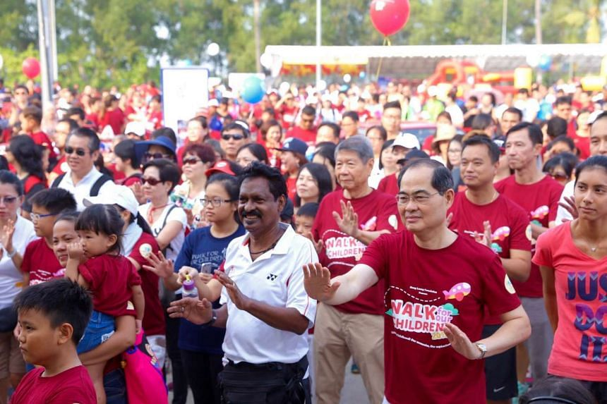 Minister Lim Hng Kiang joining the crowd for a mass warm-up before the walkathon begins.