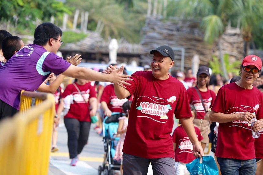 Participant Loh Kim Lian, 45, high-fiving a student cheerleader during the walk. He has participated in this annual charity walkathon several times.
