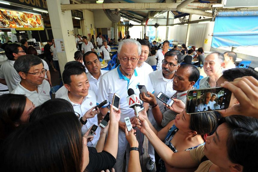 ESM Goh Chok Tong (centre) talking to reporters during a media doorstop at Bedok 538 Market and Food Centre on Sept 6, 2015.