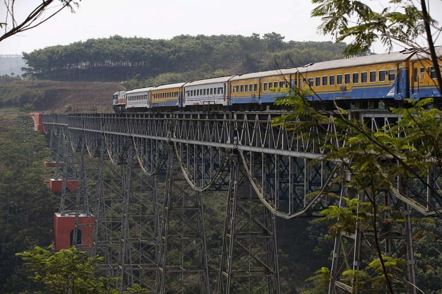 A passenger train crosses the Chikubang bridge as it travels from the city of Bandung to Jakarta near Padalarang, in West Java, on Aug 25, 2015.