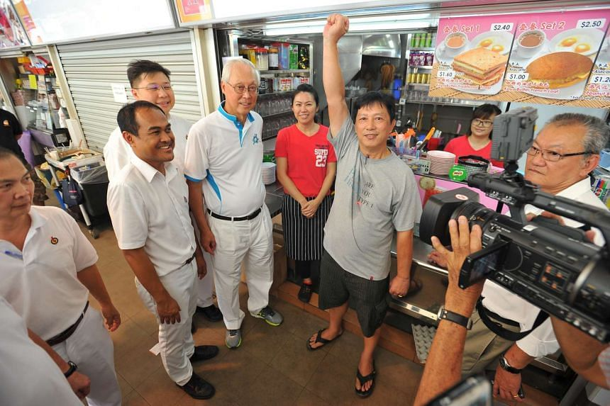 Mr Long Hian Seng, 58, partner in a stall at Bedok 538 Market and Food Centre, (raising his hand up in the air), with ESM Goh Chok Tong, and the PAP Aljunied GRC candidates, Shamsul Kamar (left, next to ESM Goh), and Chua Eng Leong (left, behind ESM