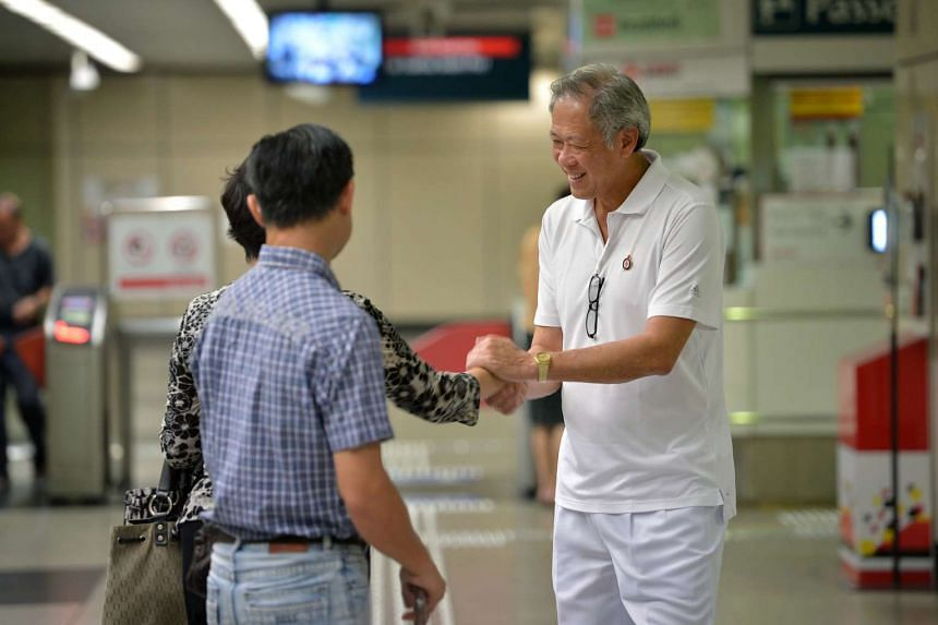Ng Eng Hen greeting commuters at Braddell MRT station on the morning of Sept 4, 2015.
