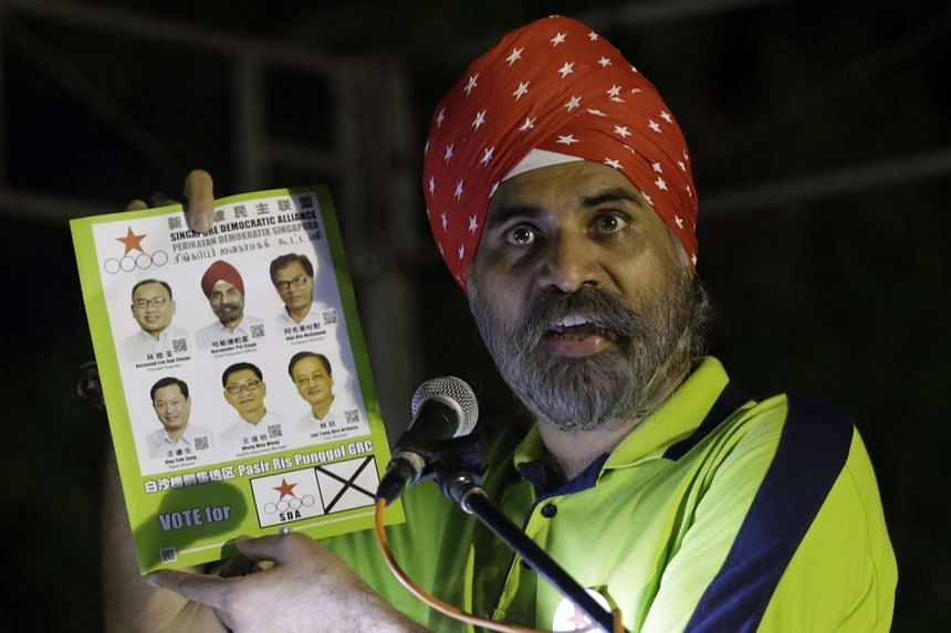 Mr Harminder Pal Singh holds up the Singapore Democratic Alliance pamphlet at a rally for Pasir Ris-Punggol GRC in Pasir Ris Park.