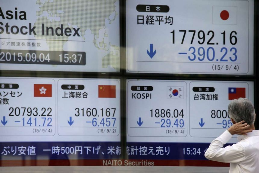 A pedestrian checking Tokyo's Nikkei Stock Average closing information (Top-R) and other Asian stock markets at a securities office in Tokyo on Sept 4, 2015.