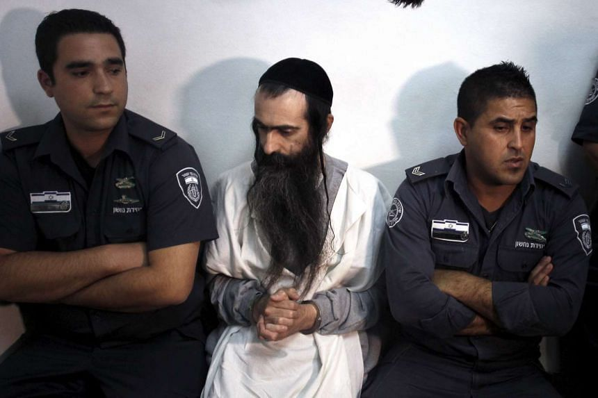 Yishai Schlissel, suspected of stabbing and wounding six participants at a Gay Pride parade in Jerusalem, is escorted by security personnel at the Jerusalem Magistrates Court on July 31, 2015.