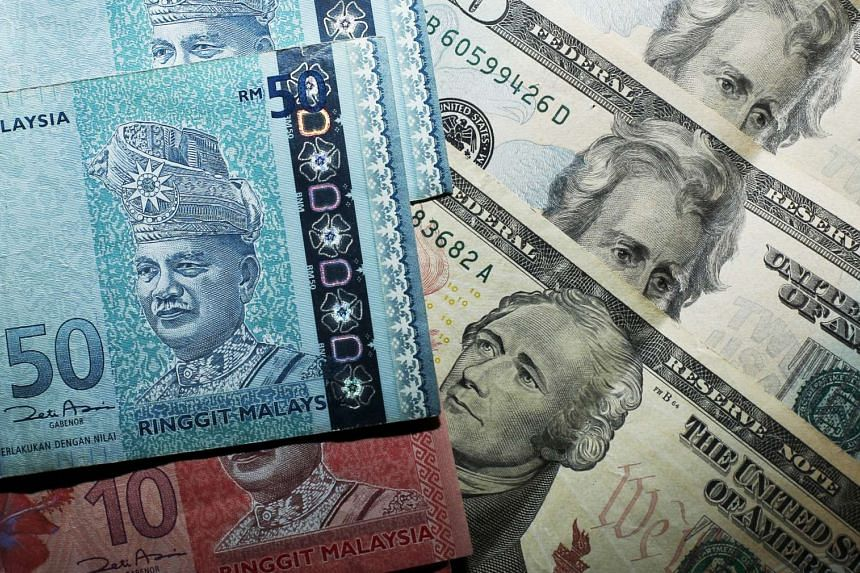 Malaysian ringgit notes are seen among US dollar bills in this photograph illustration.