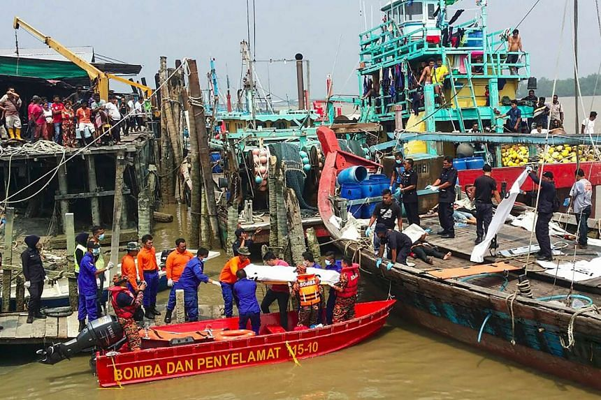 A rescue team (centre) carrying a victim retrieved from a search operation near the area where a boat carrying Indonesian migrants sank in Hutan Melintang.