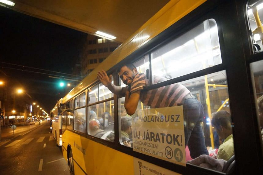 Refugees board buses Keleti Railway Station in Budapest, Hungary, early Sept 5, 2015.