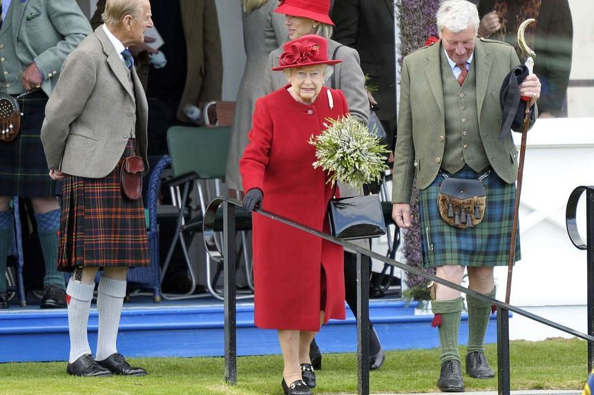 Britain's Queen Elizabeth II (centre) and Britain's Prince Philip (left) at the annual Braemar Gathering in Braemar, central Scotland, on Sept 5, 2015.