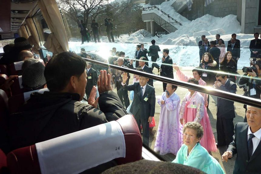 South Koreans aboard a bus waving goodbye to their North Korean relatives as they leave a family reunion at the resort area of Mount Kumgang, North Korea.