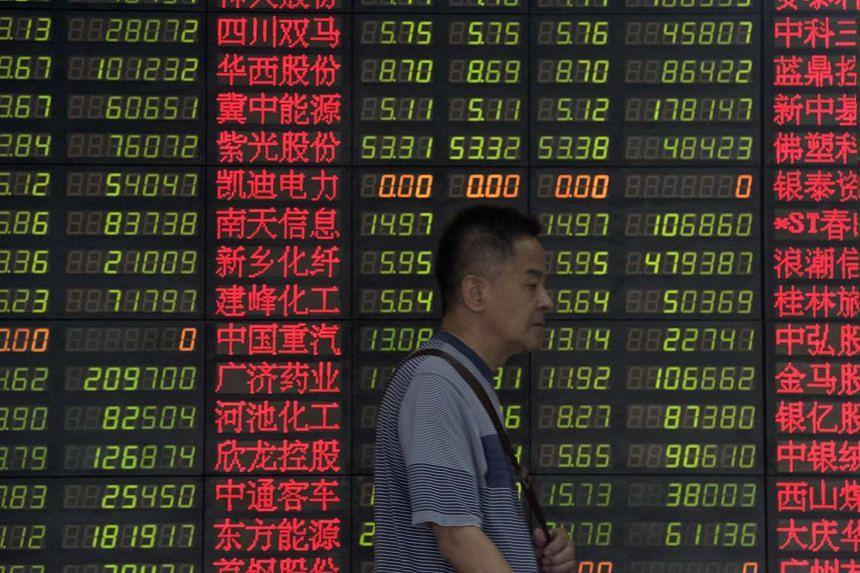 An investor walks past a digital board showing stock market movements at a brokerage house in Shanghai.