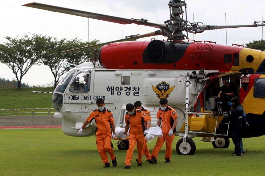 South Korean Coast Guard personnel carry the body of a passenger who was onboard a boat called Dolgorae, or Dolphin, which capsized at the sea off the southern island of Jeju in Heanam, South Korea on Sept 6, 2015.