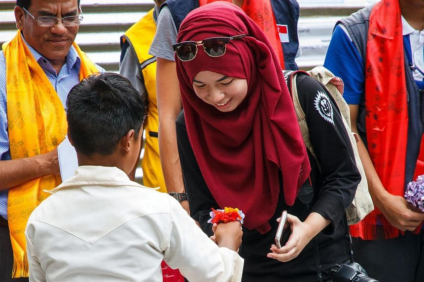 Berita Harian (BH) journalist Siti Aisyah Nordin receives a flower from a student at the Bogeswori School in Kathmandu, Nepal as she hands him a school bag and stationeries.