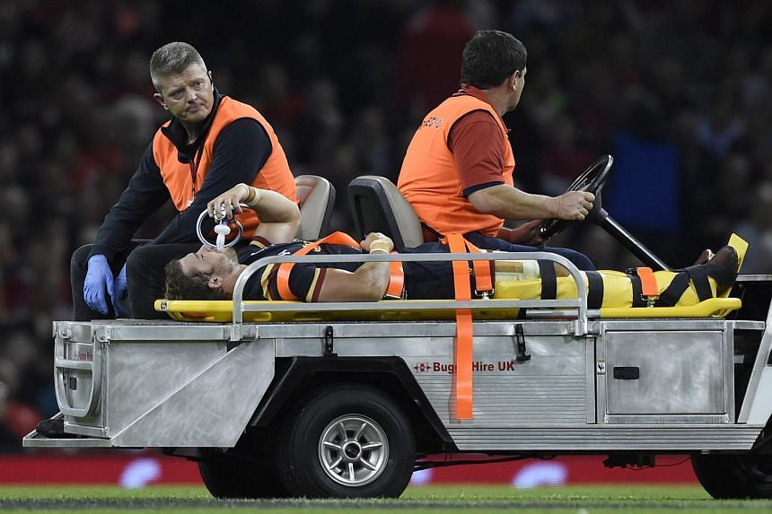 Wales' Leigh Halfpenny leaves the field injured.