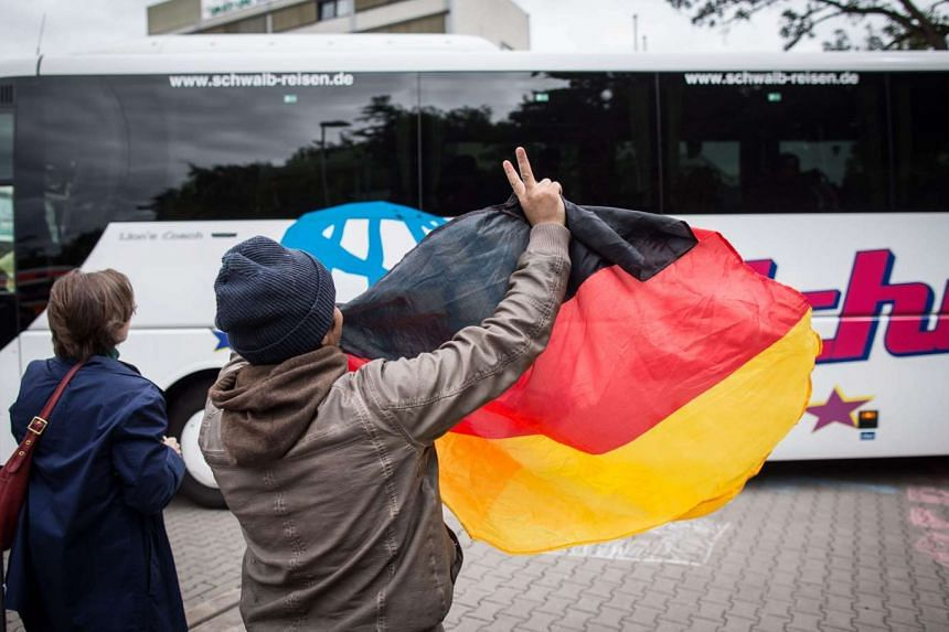 A man holds up a German flag and flashes a victory sign to greet refugees at the premises of a temporary refugee reception centre in Neu-Isenburg near Frankfurt Main, Germany, on Sept 6, 2015.