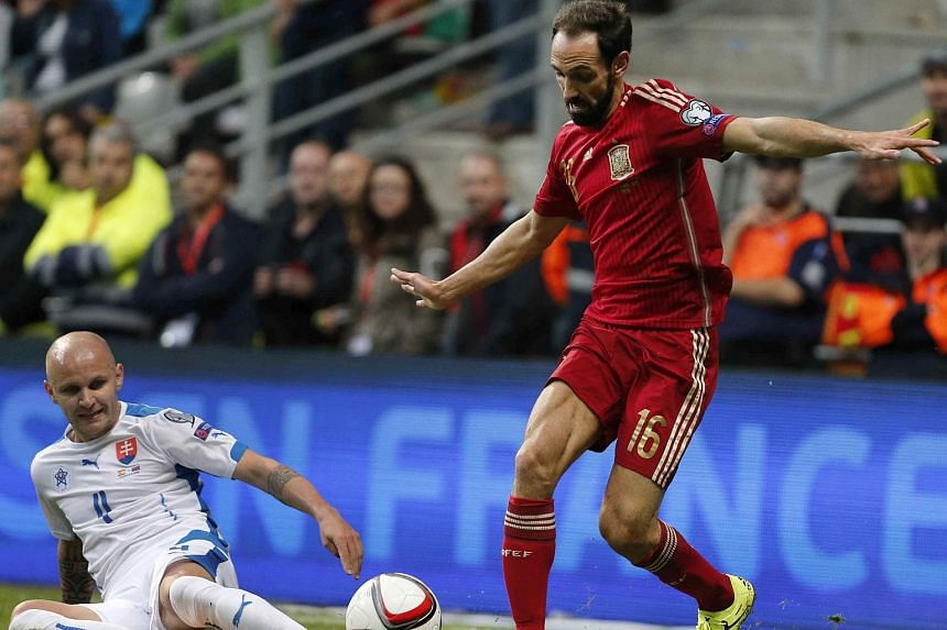 Spain's Juanfran (right) in action against Slovakia's Lukas Tesak during the UEFA EURO 2016 group C qualifying soccer match between Spain and Slovakia at Carlos Tartiere stadium, Spain on Sept 5, 2015.