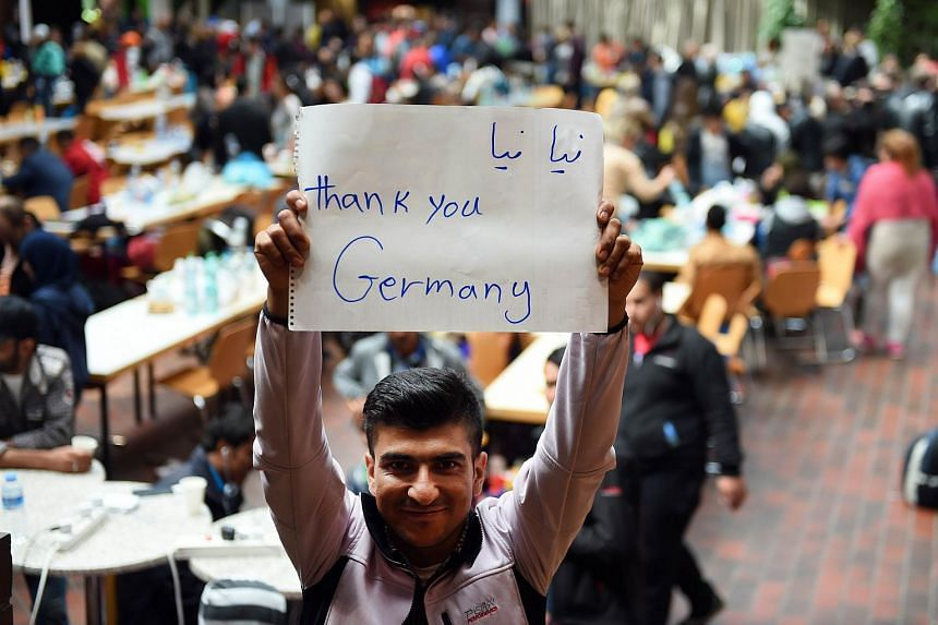"""A migrant holds a paper with the words """"Thank you Germany"""" while waiting for a bus after his arrival at the train station in Dortmund on Sept 6, 2015."""