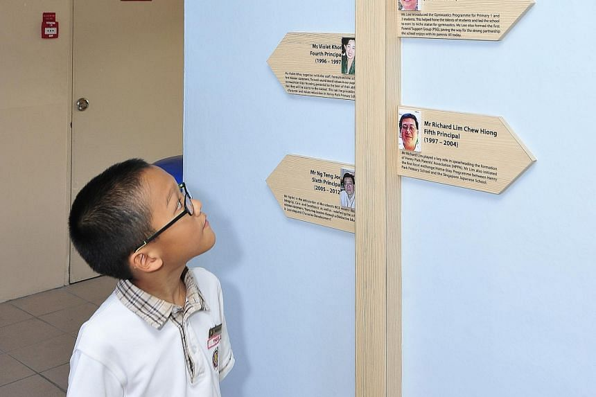 Ryan Tan with a display of past school principals of Henry Park Primary School. The 10-year-old has been trained to conduct tours for visitors at the school's heritage exhibition, which opened in April.