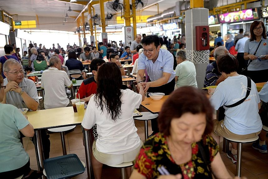 Workers' Party East Coast GRC candidate Daniel Goh greeting residents at the food centre in Block 16, Bedok South Road, during his walkabout yesterday. He said the Government should stop sending mixed signals about its immigration policy. Dr Ng Eng H